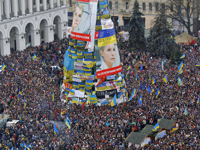 2014 год. Новогодняя елка на Майдане, на заднем плане консерватория. Сборка елки не завершена, митингующие на Майдане облепили ее плакатами с протестами.